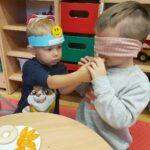 Dziecko z zawiązanymi oczami próbuje jabłko (Kopiowanie)