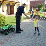 Dziewczynka podaje rękę policjantowi