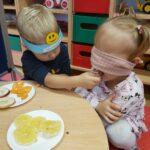 Dziewczynka próbuje marchewkę z zawiązanymi oczami