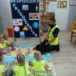 Pan policjant omawia zasady bezpiecznego zachowania podczas drogi do przedszkola i z powrotem