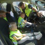 Pan policjant pokazuje dzieciom gdzie włącza sygnały świetlne i dźwiękowe w radiowozie policyjnym
