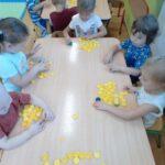 dzieci z grupy żuczki bawią się zakrętkami