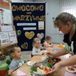 Babcia nakłada dzieciom sałatkę warzywną