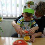 Babcia wspólnie z wnuczkiem wycina kształty z arbuza