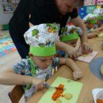 Chłopczyk kroi marchewkę