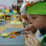 Chłopczyk kroi ugotowaną marchewkę