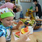Chłopczyk prezentuje owocową łódkę z kaczuszką wycietą z arbuza