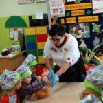 Chłopiec w stroju kucharza łączy składniki sałatki owocowo-warzywnej