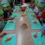 Dzieci kroją marchewkę, jabłko i por