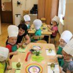 Dzieci siedzą i przy stoliku i będą wykonywały jeże