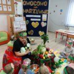 Dzieci słuchają wiersza czytanego przez babcię o warzywach