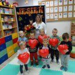Dzieci trzymają balonowe serduszka na tle jesieni z Panią Ewą Ancygier