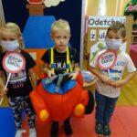 Dzieci w maseczkach z hasłem Stop smog, chłopiec przebrany w samochód