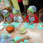 Dzieci w strojach kucharskich kroją marchew i jabłko
