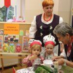Dzieci wkładają śliwki do słoika