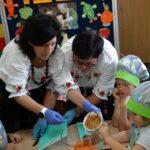 Dzieci z pomocą pań wkładają do szklanej miski skrojone jabłko