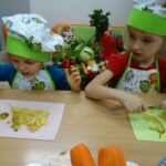 Dziecki kroją ugotowane warzywa