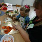 Dzieczynka z babcią dekoruje kurczaczka warzywnego