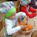 Dziewczynka miesza składniki sałatki owocowo-warzywnej