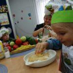 Dziewczynka trze na tarce jabłko