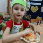Dziewczynka trze na tarce surową marchewkę