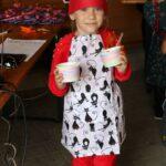 Dziewczynka w stroju kucharza z sałatką owocową
