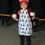 Dziewczynka w stroju kucharza z sałatką owocową.