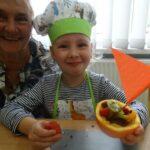 Dziewczynka z babcią prezentuje wykonaną własnoręcznie łódkę owocową