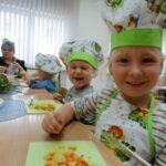 Dziewczynka z chłopcem prezentują pokrojone własnoręcznie ugotowane warzywa