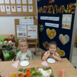 Dziewczynki siedzą przy stoliku na którym znajdują się kurczaki i kogut warzywny