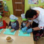 Pani z zespołu Jarzębina pokazuje dzieciom jak kroić marchewkę